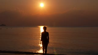 Young Woman Silhouette in Sea against Sunset.