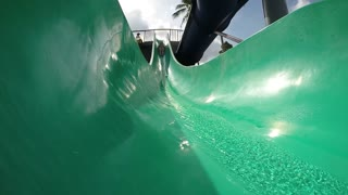 Young Woman Sliding in Tube in Water Park. Slow Motion.