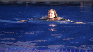 Young Woman Swimming in Blue Water Pool on Vacation in Resort
