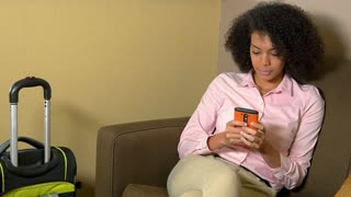 Attractive African American businesswoman sending text and ready for airport