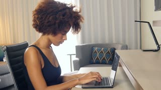African American businesswoman working from home on laptop computer