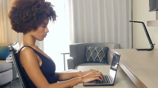 African American businesswoman working on laptop computer while traveling