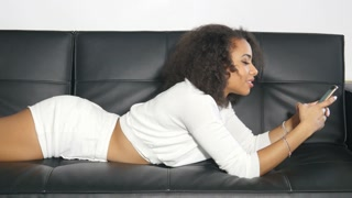 African American girl student sending text message in college dorm