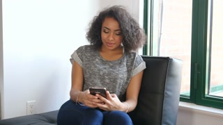African American teenager girl sending text message in urban loft