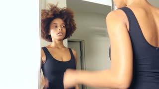 African American woman getting ready for work in mirror