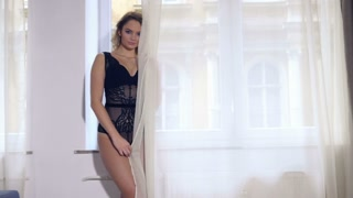 Attractive blond woman in lingerie waiting by window alone