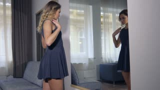 Attractive businesswoman getting ready in mirror before work