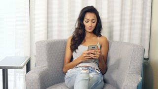 Attractive ethnic Indian girl sending text message