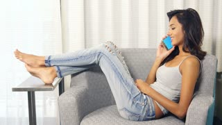 Attractive Indian ethnic woman talking on mobile smart phone