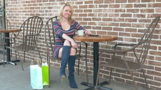 Attractive mature blond consumer woman sitting at cafe