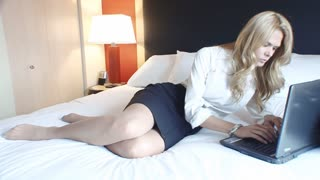 Beautiful blond mature business woman working on laptop