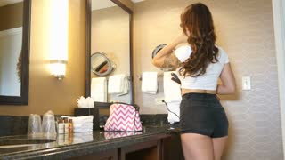 Beautiful hipster girl fixes hair in mirror