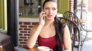 Beautiful woman talking on mobile phone at cafe