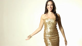 Beautiful young woman dancing in gold dress and blowing kiss