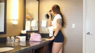 Beautiful young woman getting makeup ready in mirror before date