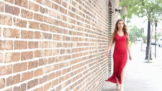Beautiful young woman walking into focus in red dress - Urban