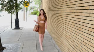 Beautiful young woman walking into focus on shopping trip in city