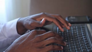 Black businessman hands typing on computer