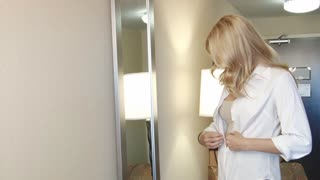 Blond business woman dressing in mirror for work
