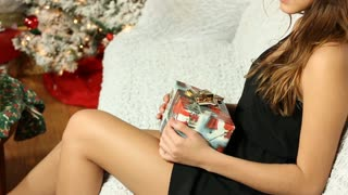 Crop of female teen holding Christmas gift in her hand and smiling