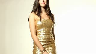 Dancing girl in gold dress pan up on body and face