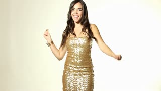 Dancing girl in tight gold dress points at camera