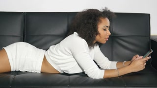 Ethnic girl sending text message while lying on leather couch