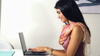 Ethnic girl working on laptop computer