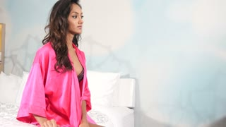 Ethnic woman in lingerie and robe in bedroom beauty portrait