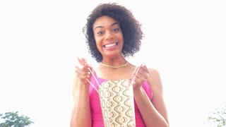 Excited African American consumer woman with shopping bag outdoors