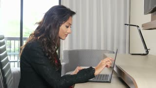 Excited Indian business woman working on laptop computer touchscreen