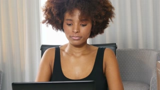 Frustrated African American woman working on laptop computer at home