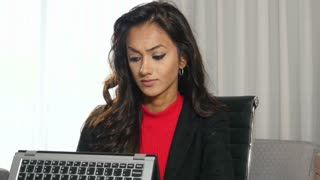 Frustrated ethnic businesswoman using touchscreen hybrid laptop computer