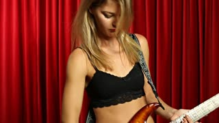 Girl dancing with electric guitar while playing music