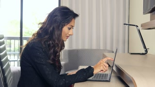 Happy ethnic Indian woman working on laptop touchscreen computer