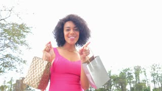 Happy excited African American woman dancing with shopping bags