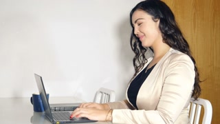 Happy plus size woman working in office on laptop computer
