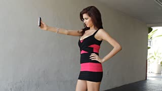 Happy sexy fashion girl latina taking self portrait with mobile phone