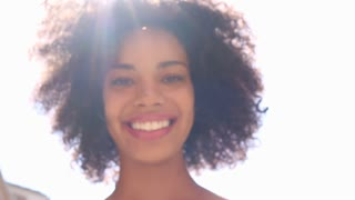 Happy smiling african american woman with lens flare outdoors