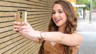 Happy teen girl taking selfie with her cell phone in urban setting