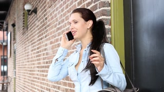 Happy young businesswoman talking on mobile phone