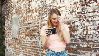 Happy young woman with vintage camera in urban scene