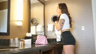 Hipster girl fixing hair in mirror with tattoo on arm