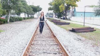 Hipster rock and roll girl walking towards camera on rail road tracks