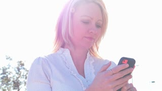Lens flare on mature blonde woman sending text message and looking away