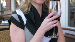 Mature blond woman drinking wine at cafe 4k