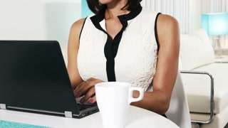 Pan up ethnic business woman working on computer with coffee