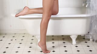 Pan up on bikini girl slow motion in bathroom