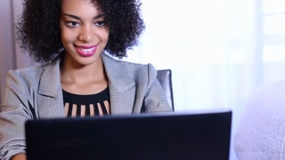 Pan up on young African American business woman working on laptop