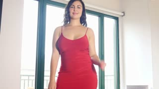 Plus size model woman dancing in red dress